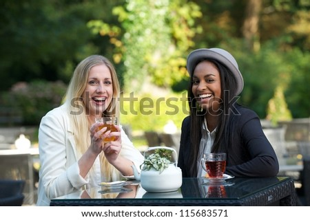 Two beautiful women drinking tea and  and chatting at an outdoors cafe.
