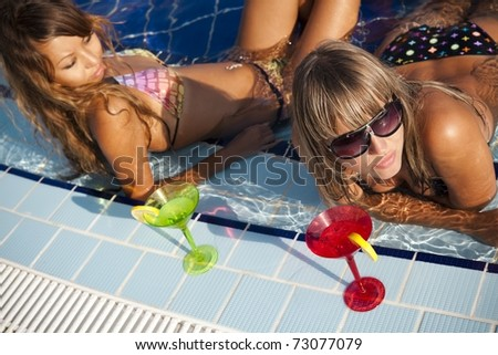 Two beautiful  women enjoying teir summer vacation with a glasses of martini - stock photo