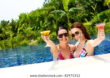 Two beautiful women enjoying their summer vacation with cocktails by the pool - stock photo