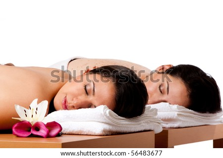 Two beautiful women friends laying on wooden tables with head on towels waiting for their massage in the spa, isolated. - stock photo