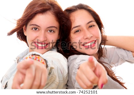 Two beautiful women happy and pointing forward - stock photo