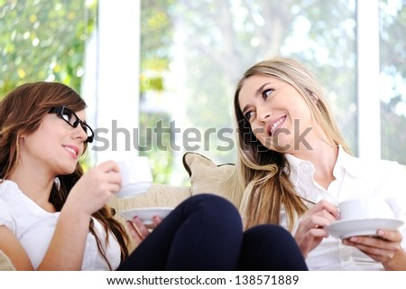 Two beautiful women having conversation drinking coffee and sitting on couch - stock photo