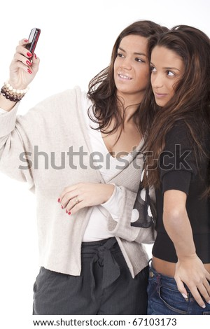 two beautiful women having fun and taking pictures with their cellphone