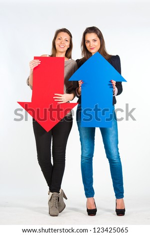 Two beautiful women holding red and blue arrow, up and down - stock photo