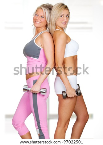 Two beautiful women in fitness outfit using weights