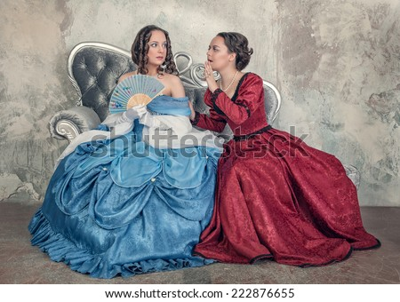 Two beautiful women in medieval dresses gossip on the sofa - stock photo