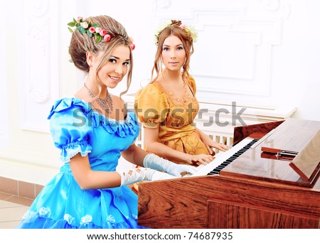 Two beautiful women in medieval era dresses playing the piano. - stock photo