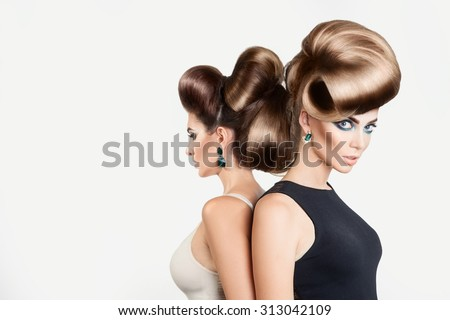 Two beautiful women in studio. Both with creative hairstyle and nice makeup on gray background - stock photo