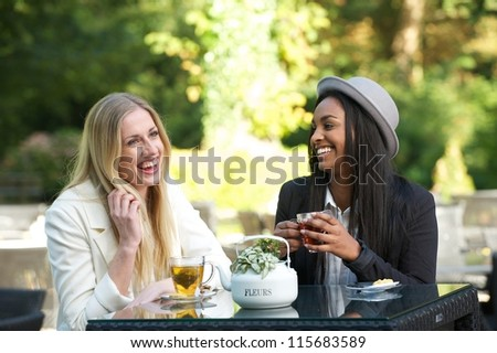 Two beautiful women laughing and smiling outdoors