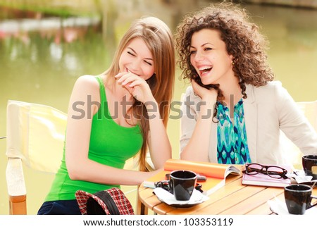 Two beautiful women laughing over a coffee at the river side terrace - vibrat summer colors - stock photo
