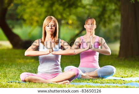 Two beautiful women meditating in the park - stock photo