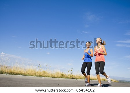 Two beautiful women on morning run outdoors - stock photo
