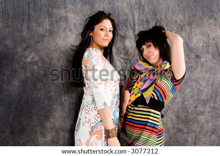 Two beautiful women posed back to back one dressed in a modern dress and one in a retro pop art pattern outfit - stock photo