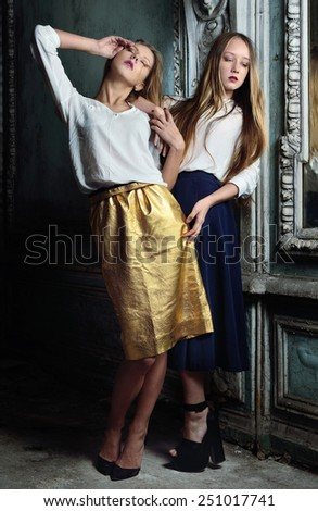 Two beautiful women posing in obsolete interior. Studio with interior of old palace. Not necessary property release. - stock photo