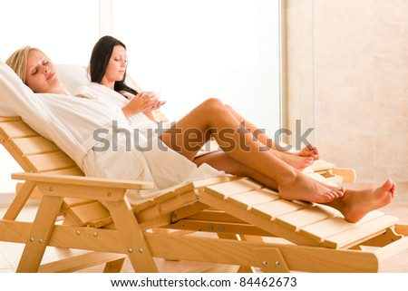 Two beautiful women relax sitting on sun-beds healthy luxury spa - stock photo