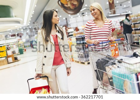 Two beautiful women shopping in supermarket