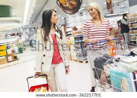 Two beautiful women shopping in supermarket - stock photo