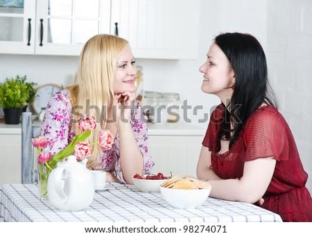 Two beautiful women talking in the kitchen - stock photo