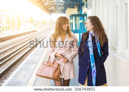 Two beautiful women walking along platform at train station. They are happy, smiling and looking each other. Autumn or winter setting, they are both wearing a coat. Travel and lifestyle concepts. - stock photo