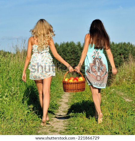 Two beautiful women walking at the meadow with busket with apples. - stock photo