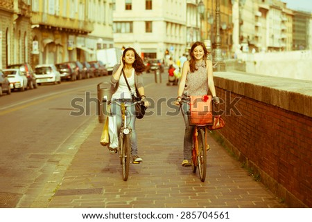 Two Beautiful Women Walking in the City with Bicycles and Bags - stock photo