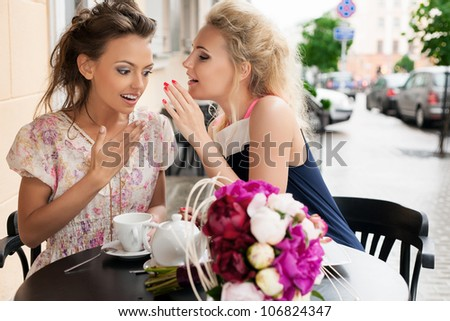 Two beautiful women with great smile and hairstyle whispering.