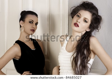 two beautiful women with hair style and elegant dress posing indoor near an old fashion door posing while looking towards camera - stock photo