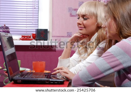 two beautiful women with laptop at the kitchen