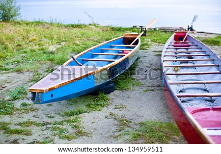 two Beautiful wooden red and blue canoe on shore of pretty coast - stock photo