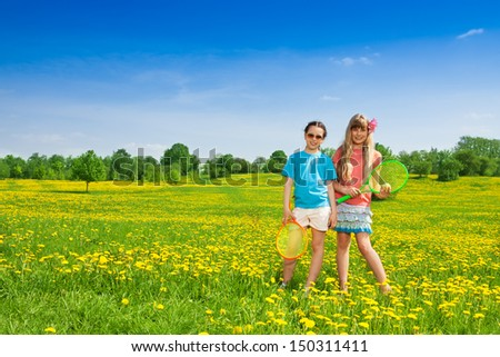 Two beautiful 10 year old girls with tennis racquets standing in flower field