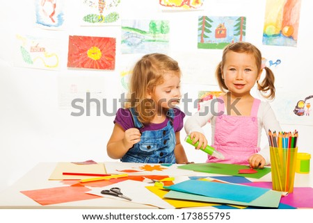 Two beautiful 3-4 years old girls cutting and gluing color cardboard  - stock photo