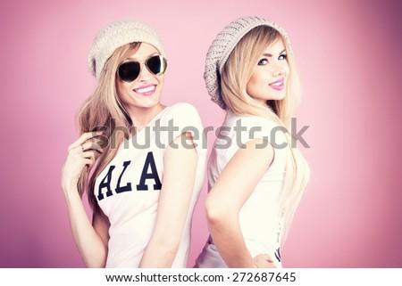 Two beautiful young blonde woman posing together, having fun. Girls smiling. Fashion photo. Studio shot. - stock photo