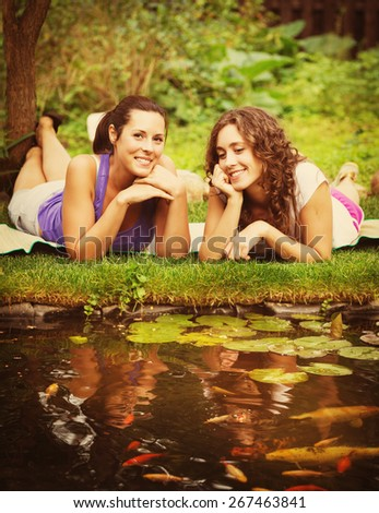 Two beautiful young brunet woman outdoors nature - stock photo