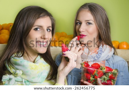Two beautiful young Caucasian girls eating strawberries from punnet in fruit market - stock photo