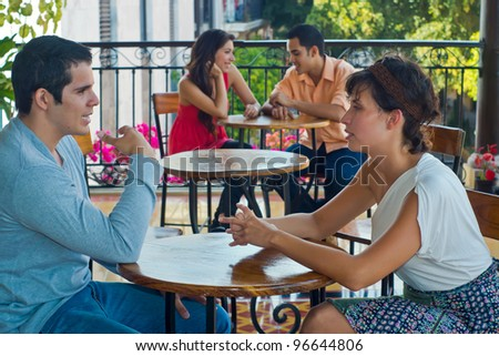 Two beautiful young couples being intimate at restaurant tables - stock photo