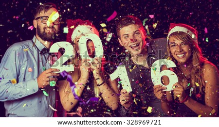 Two beautiful young couples having fun at New Year's Eve Party, holding cardboard numbers 2016 - stock photo
