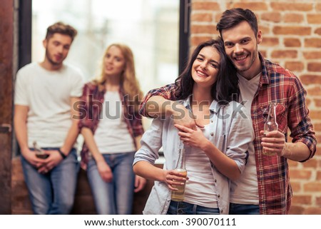 Two beautiful young couples in casual clothes are resting with bottles of drink and smiling. Couple in the foreground is cuddling - stock photo