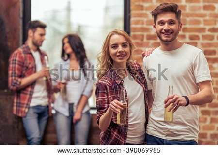 Two beautiful young couples in casual clothes are resting with bottles of drink, talking and smiling - stock photo