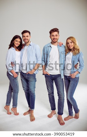 Two beautiful young couples in jeans are looking at camera and smiling, standing barefoot on a gray background - stock photo