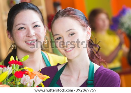 Two beautiful young female employees in a busy flower shop - stock photo