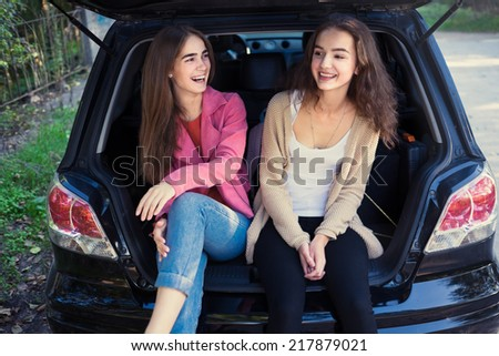 Two beautiful young girl resting in the car - stock photo