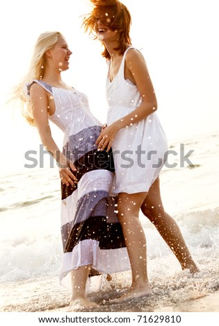 Two beautiful young girlfriends on the beach at sunrise. Photo with counter-light on background. - stock photo