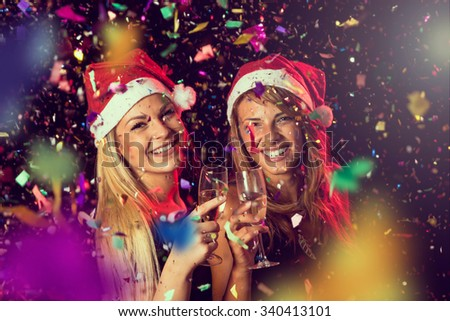 Two beautiful young girls having fun at New Year's Eve party, toasting each other at midnight - stock photo