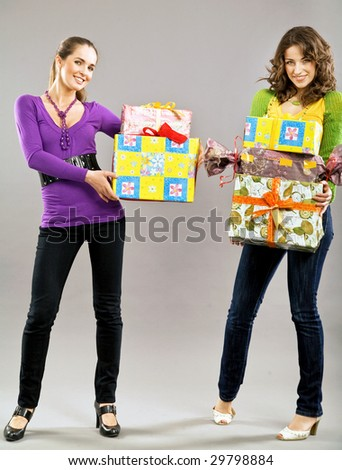 Two beautiful young girls holding  presents - stock photo