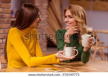 Two beautiful young girls in casual clothes communicating, drinking coffee and smiling, while sitting in cafe - stock photo