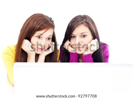 two beautiful, young girls in front of laptop - stock photo