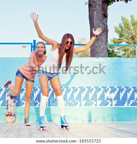 two beautiful young girls on the floor of an empty pool, one pushes the other in roller skates - stock photo