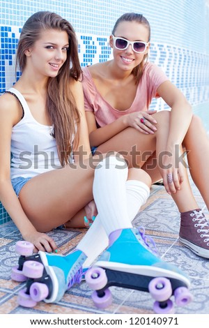 two beautiful young girls on the floor of an empty pool smiling for the camera - stock photo