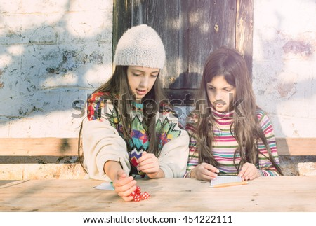 Two beautiful young girls play a board game with dice on a sunny winter day. Countryside background, cross process sunny glow look. - stock photo