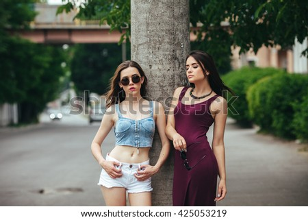 Two beautiful young girls posing on the background of the urban landscape